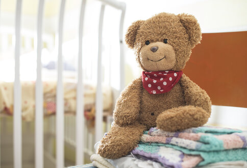 Stack of blankets and a teddy-bear on a chair - DEGF000523