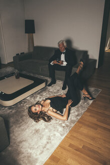 Senior man with drink on sofa looking at young woman lying on carpet - CHAF001460