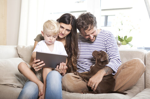 Parents, little son and their dog sitting together on the couch - MFRF000392