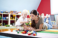 Mother playing with her little son on the carpet of children's room - MFRF000409