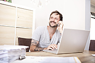 Smiling man sitting at wooden table with laptop and folder telephoning with smartphone - MFRF000425