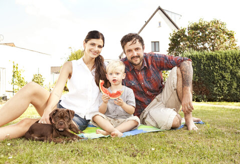 Parents sitting with their little son and dog on a blanket in the garden - MFRF000434