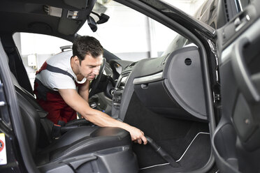Car cleaning, man hoovering car interior - LYF000474