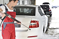 Car cleaning, man cleaning car with high-pressure cleaner - LYF000493