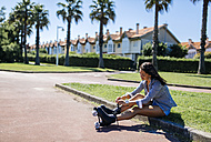 Spain, Gijon, teenage girl sitting on curb tying her roller skates - MGOF000983