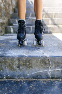 Legs of a teenage girl with roller skates on stairs - MGOF000993