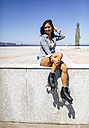 Spain, Gijon, smiling teenage girl with roller skates sitting on a wall - MGOF000995