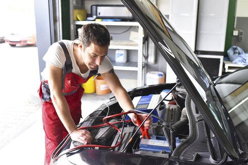 Car mechanic working in repair garage, reloading car battery - LYF000528