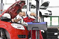 Car mechanic working in repair garage, setting car headlights - LYF000516
