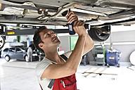 Car mechanic working in repair garage, repairing unterbody - LYF000527
