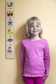 Portrait of smiling little girl standing beside a yardstick - JFEF000696