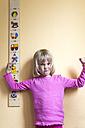 Portrait of grimacing little girl standing beside a yardstick - JFEF000699