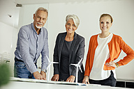 Three smiling business people with wind turbine model on conference table - MFF002144