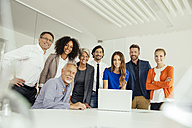 Portrait of smiling business people with laptop in conference room - MFF002147