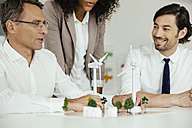 Business people discussing wind turbine model and houses on conference table - MFF002153