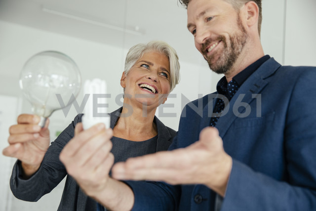 Businesswoman and businessman comparing regular and energy-saving lightbulb - MFF002159