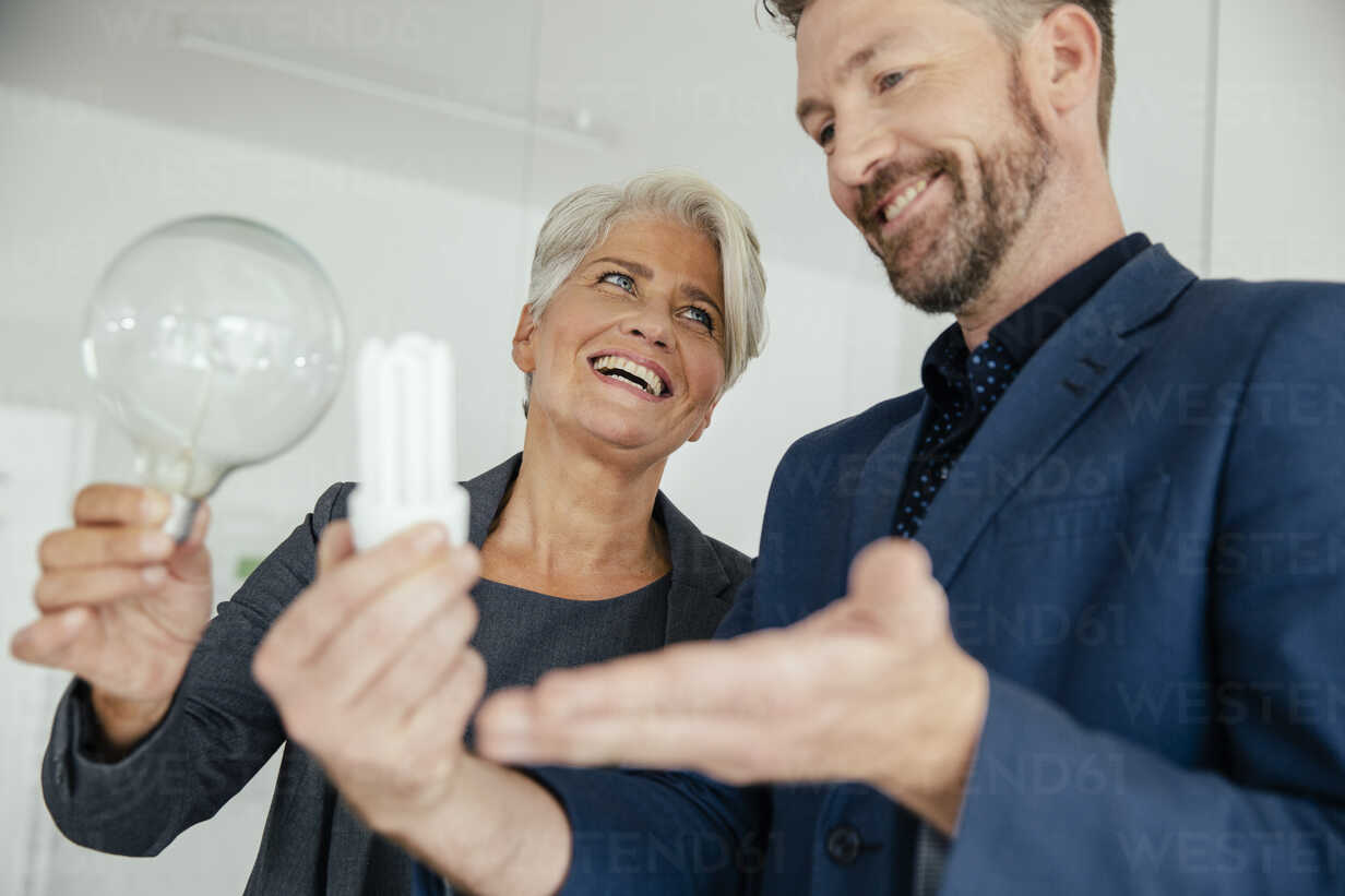 Businesswoman and businessman comparing regular and energy-saving lightbulb - MFF002159 - Mareen Fischinger/Westend61