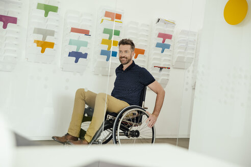 Smiling man in wheelchair in modern office - MFF002162