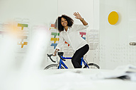 Smiling young woman with bicycle in office waving - MFF002179