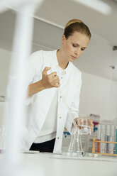 Female scientist mixing liquids in lab - MFF002191