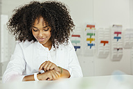 Female scientist in lab looking at smartwatch - MFF002203