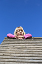 Portrait of blond little girl on wooden hut looking at distance - JFEF000691
