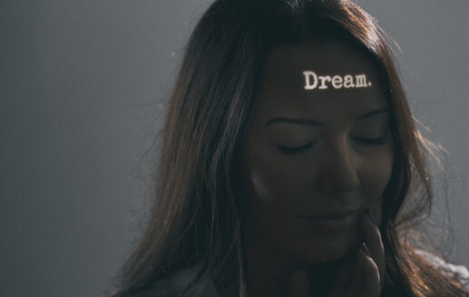 Woman with the word dream projected on her forehead - SEL000067