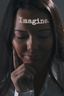 Portrait of woman with the word imagine projected on her forehead - SEL000069
