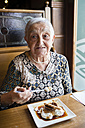 Senior woman eating caramel custard in a restaurant - RAEF000489