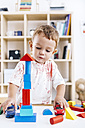 Portrait of excited little boy playing with building bricks and toy cars - JRFF000062