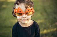 Portrait of little girl wearing halloween glasses shaped like pumpkins - MGOF000666