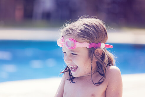 Portrait of laughing little girl with swimming goggles in front of a pool - XCF000005