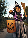 Portrait of little girl masquerade as a witch with halloween lantern and broom - MGOF000706