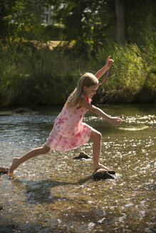Girl walking through a brook - SARF002102