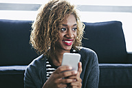 Portrait of smiling young woman with her smartphone - EBSF000892