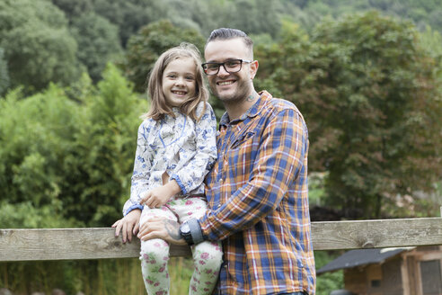 Smiling father with daughter outdoors - XCF000013