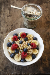 Bowl of muesli with banana slices, raspberries and blueberries - EVG002224