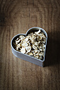 Rolled oats in a heart-shaped cookie cutter on white wood - EVGF002237