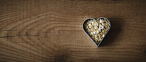 Rolled oats in a heart-shaped cookie cutter on wood - EVGF002239