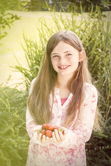 Portrait of smiling girl with handful of strawberries - JUNF000430
