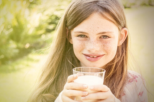 Portrait of smiling girl holding glass of milk - JUNF000431