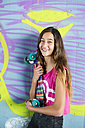 Portrait of smiling teenage girl holding a colorful skateboard in front of wall with graffiti - GEMF000371