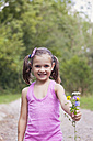 Portrait of smiling little girl showing flowers - XCF000019