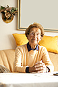 Portrait of aged woman sitting on couch in her living room - MFRF000461