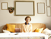 Portrait of aged woman sitting on couch in her living room - MFRF000463