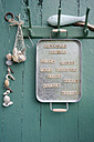 Old metal tray with magnetic scrabble tiles used as shopping list hanging on coat rack - GISF000156