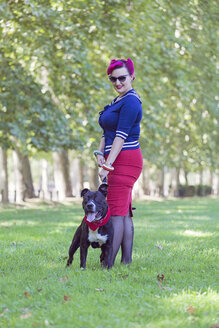 Portrait of woman with dyed hair standing on a meadow with her pit bull terrier - XCF000023