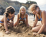 Spain, Colunga, three girls playing on the beach - MGOF000711