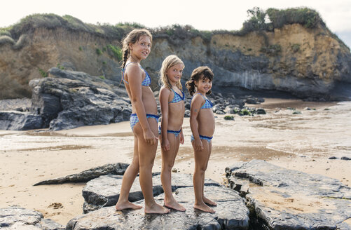 Spain, Colunga, three girls standing in a row on the beach - MGOF000712