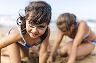 Portrait of smiling little girl playing on the beach - MGOF000718